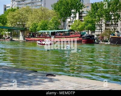 People boating on the Bassin Villette on a sunny, Saturday afternoon in April. Paris, France. - Stock Photo