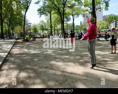 People playing pétanque in the shade alongside the canal on a warm, April afternoon.Bassin de la Villette, Paris, France. - Stock Photo