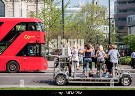 Women enjoying a fun day out in London UK, near St. Paul's Cathedral. Iconic red London bus can also be seen in the photo. - Stock Photo