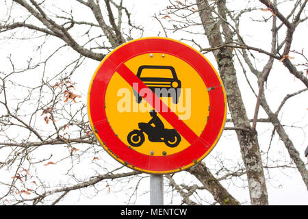European round traffic sign, the passage of vehicles and motorcycles prohibited. On autumn trees background - Stock Photo