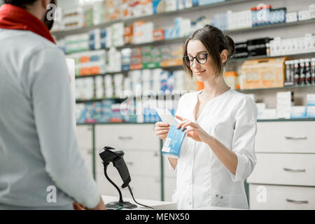 Pharmacist selling medications in the pharmacy store - Stock Photo