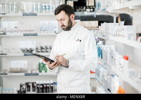 Pharmacists working in the pharmacy store - Stock Photo