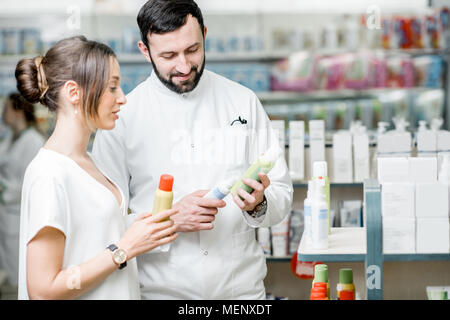 Pharmacist with client in the pharmacy store - Stock Photo