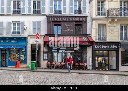 A man crosses the road outside Le Relais Gascon restaurant , Rue des Abbesses, Montmartre , Paris , France - Stock Photo