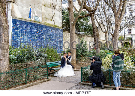 Chinese Bride and Groom pose for pictures in front of Le Mur des je taime, Wall Of I Love You ,in Jehan Rictus Square , Abbesses, Montmartre, Paris - Stock Photo