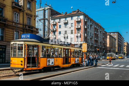 Milan, Italy - April 21st, 2018: Passengers boarding a traditional yellow tramsway in a busy city centre - Stock Photo
