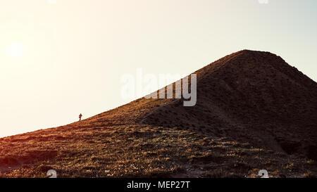 A traveler climbs a mountain - Stock Photo