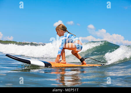 Happy baby girl. young surfer ride on surfboard with fun on sea waves. Active family lifestyle, kids outdoor water sport lessons and swimming activity Stock Photo