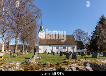 Sogne, Norway - April 21, 2018: Old Sogne Church. White wooden church in Sogne, a parish church in Sogne, Vest-Agder in Norway. Blue sky, green grass. - Stock Photo