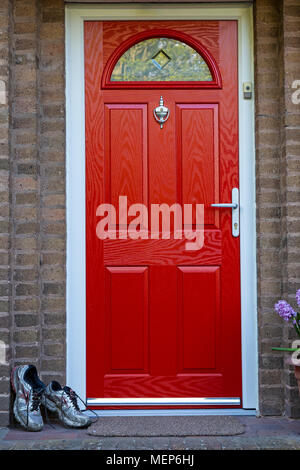 A pair of muddy running shoes left outside a house by a bright red door. - Stock Photo