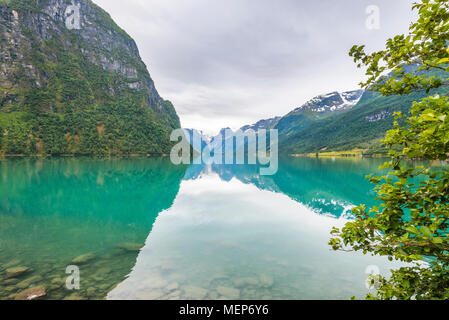 Lake Oldevatnet with mirroring, view to the Briksdalsbreen glacier, Norway, near Olden at the Nordfjorden, mountainscape in the Oldedalen valley - Stock Photo