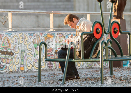 A man sits on a park bench and works his smartphone as the sun sets along the Atlanta Beltline in the Old 4th Ward on December 5, 2015 in Atlanta, GA. - Stock Photo
