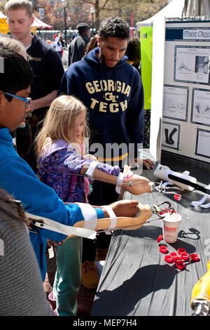 Kids attempt to drop bottle caps into a cup using a prosthetic arm and hooks, at the Atlanta Science Fair on March 28, 2015 in Atlanta, GA. - Stock Photo