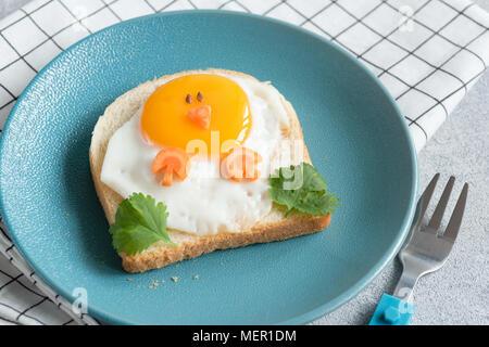 Funny chicken sandwich for kids on a blue plate. Food art, creative idea for children breakfast menu. Closeup view. - Stock Photo