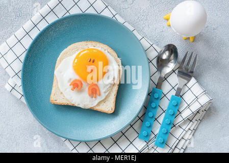 Funny egg toast for kids on blue plate, top view. Chicken shaped sandwich, food art. - Stock Photo