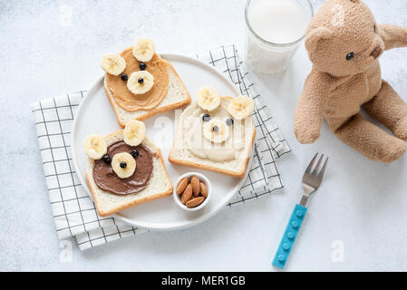 Funny food art breakfast toast for kids. Teddy bear nut butter toasts on white, top view - Stock Photo