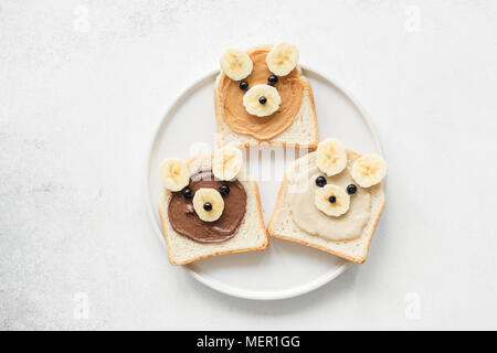 Funny animal face toasts with nut butter, banana and blueberries on white plate. Kids meal. Vegan, vegetarian, healthy lifestyle, healthy eating conce - Stock Photo