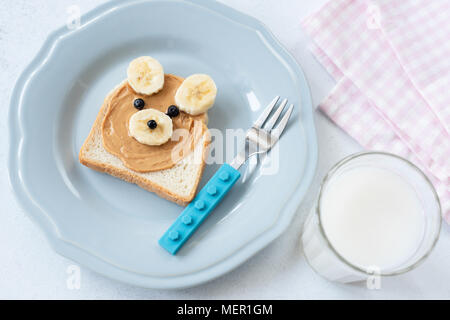 Peanut butter and banana toast in Teddy Bear shape and glass of almond milk. Funny food art for kids. Top view. Healthy eating concept - Stock Photo