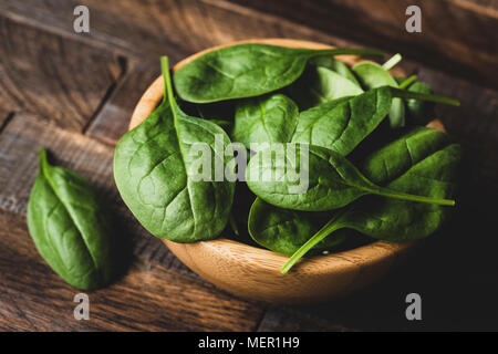 Baby spinach in wooden bowl, closeup view selective focus. Dieting, healthy eating, healthy lifestyle, fitness, weight loss concept - Stock Photo