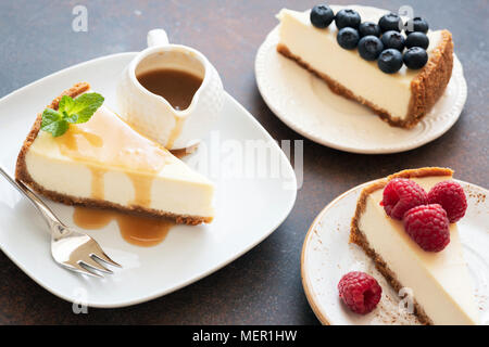 Assortment of cheesecakes with different toppings. Cheesecake with raspberries, cheesecake with caramel sauce and cheesecake with blueberries