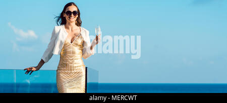Woman drinking sparkling wine looking over ocean - Stock Photo