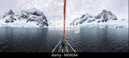 Panoramic view of sailboat bow or prow in the famous Lemaire Channel in the Antarctic Peninsula. Surrounded by mountains and glaciers while sailing in - Stock Photo