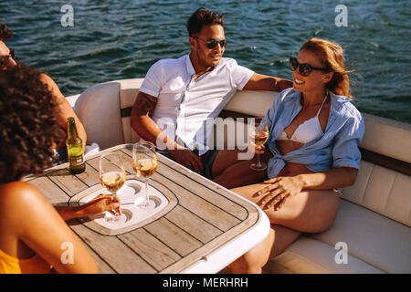 Group of young men and women enjoying at yacht party. Young friends partying on a boat. They are sitting at the back of the boat and drinking wine. - Stock Photo