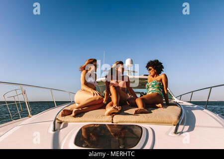 Group of young women sitting on the yacht deck sailing the sea. Three female friends in swimsuits relaxing and talking on the bow of a luxury yacht. - Stock Photo