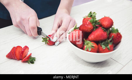 A close up image of a girls hands holding a knife and preparing fruit by slicing strawberries in her kitchen