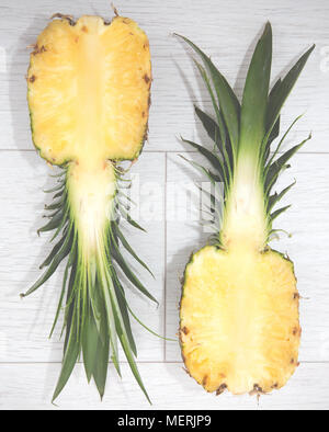 Looking down from above onto a pineapple that has been sliced into two halves revealing the inside of the fruit flesh in a cross section - Stock Photo