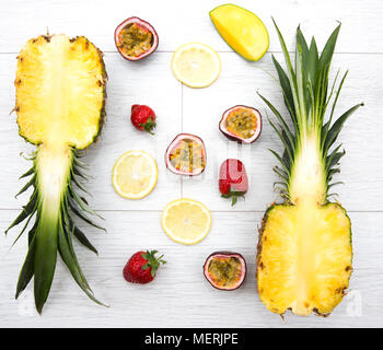 Looking down from above onto the fresh fruit such as passion fruit,mango, strawberry and pineapple which are the ingredients for a tropical smoothie. - Stock Photo