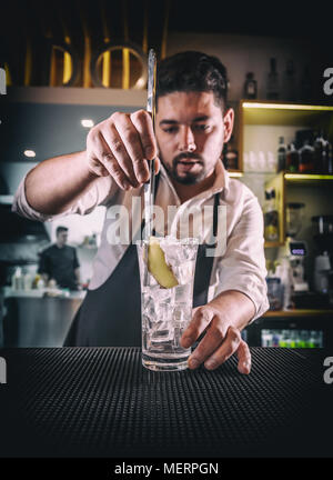 Bartender in a white shirt and black apron, adding a slice of ginger into a glass - Stock Photo