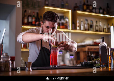 Bartender decorating non-alcoholic pomegranate cocktail with lime slices - Stock Photo