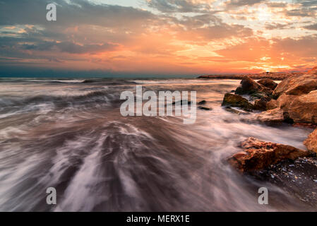 Sunrise over the sea. Stone on the foreground. - Stock Photo