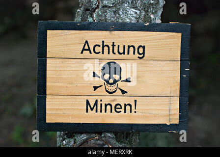 German land mines warning sign from World War Two, wet with water droplets. - Stock Photo