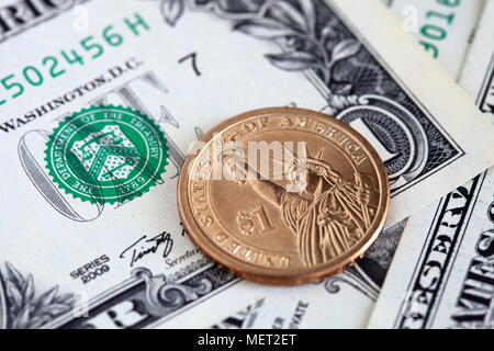 Close up of US dollar bills and one dollar coin - Stock Photo