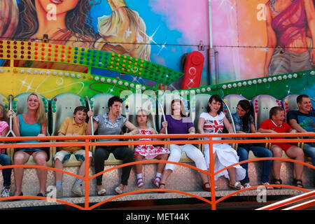 Russia, Bryansk, 11 June 2012. Happy people ride on carousels in Luna Park. - Stock Photo