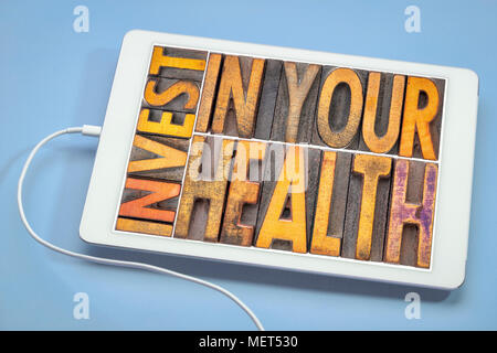 invest in your health concept - word abstract in vintage letterpress wood type on a digital tablet - Stock Photo