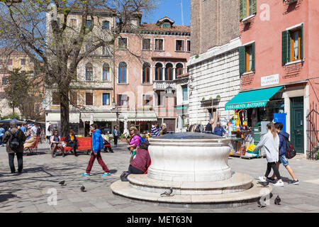 The ancient well head or pozzo in Campo Santi Apostoli, Cannaregio, Venice, Veneto, Italy with people enjoying a sunny spring day - Stock Photo
