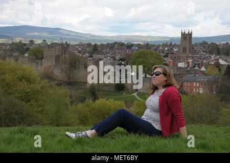 A woman relaxing on Whitcliffe Common with Ludlow Castle in the background. - Stock Photo