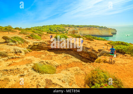 Benagil, Portugal - August 23, 2017: Benagil Cave seen from the top of rocky cliff in Algarve coast, Lagoa, Portugal. People watching the impressive sea caves from above. Summer holidays. - Stock Photo