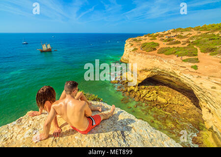 Benagil, Portugal - August 23, 2017: Lifestyle couple in summer holidays, sunbathing on cliffs in Algarve coast famous for its rock formations. Benagil Cave, a popular sea cave on the cliff in front. - Stock Photo