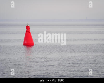 Red buoy as a navigation mark in the calm sea - Stock Photo