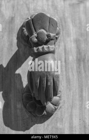 Isolated, close-up of an ornate old metal door knocker in the shape of a hand, mounted on a grainy wooden door, with a shadow, in black and white - Stock Photo