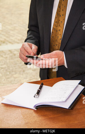 Close up of hands of well dreassed businessman at office desk texting on his cell phone - Stock Photo