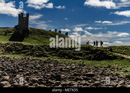 Walkers on the Northumberland Coast Path passing the ruins of Dunstanburgh Castle. Near Craster, Northumberland, UK. - Stock Photo