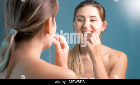 Portrait of young woman checking her teeth at mirror - Stock Photo