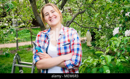 Portrait of laughing young woman next to garden stepladder in orchard - Stock Photo