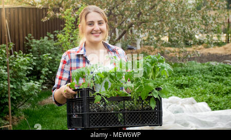 Portrait of happy female gardener holding crate with seedlings - Stock Photo