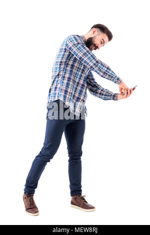 Furious young bearded business man punching mobile phone display with fist. Full body isolated on white background. - Stock Photo